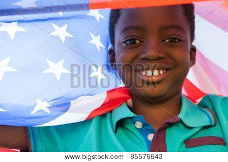Happy boy in the park with american flag on a sunny day