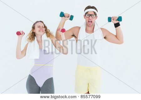 Geeky hipster couple lifting dumbbells in sportswear on white background
