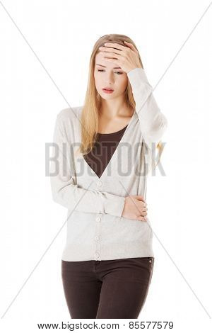 Full length young woman with huge headache.