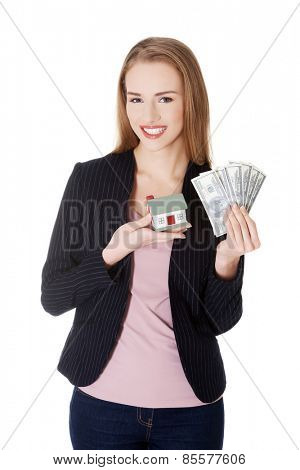 Businesswoman holding house model and dollar bills.