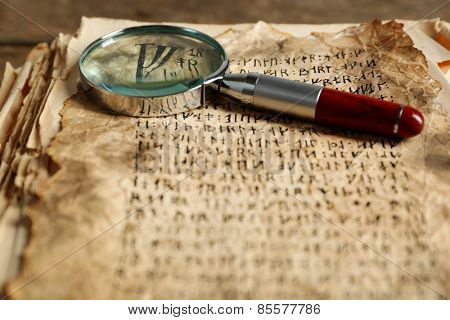 Grunge papers with hieroglyphics with magnifier close up