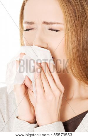 Close up woman holding tissue sneezing.