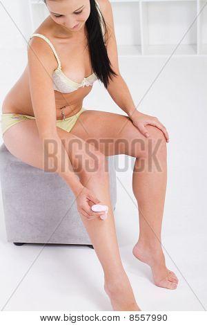 woman moisturising legs