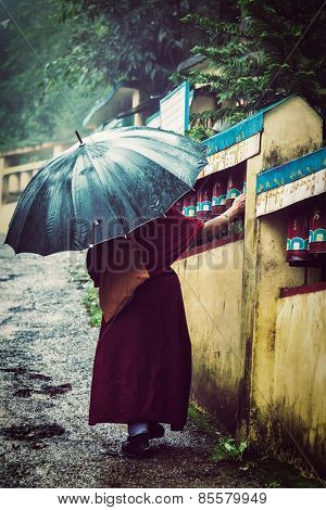 Vintage retro effect filtered hipster style image of  Buddhist monk spinning prayer wheels in McLeod Ganj, Himachal Pradesh, India. The text is