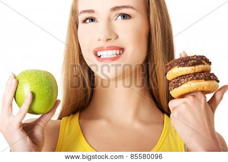 Woman has a hard choice between donut and apple.