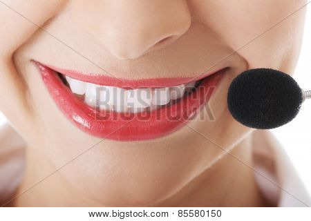 Smiling telemarketing operator with microphone.
