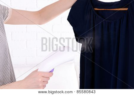 Women steaming dress in room