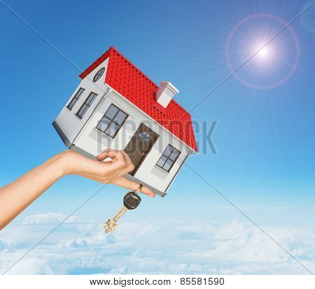 White house and keys in hand with red roof, brown door, chimney. Background sun shines brightly