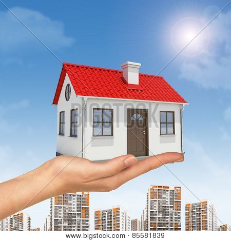 White house in hand with red roof, chimney. Background building, sun shines brightly