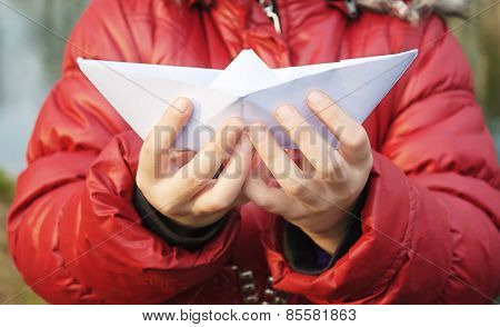 Hands Holding A Paper Boat Closeup Outside