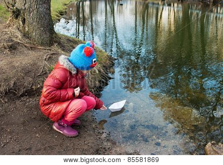 Little Girl Let A Paper Boat On The River Outside