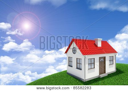 White house with red roof on green grassy hill. Background sun shines brightly, clouds