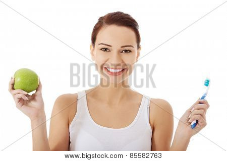 Portrait of woman holding an apple and toothbrush.