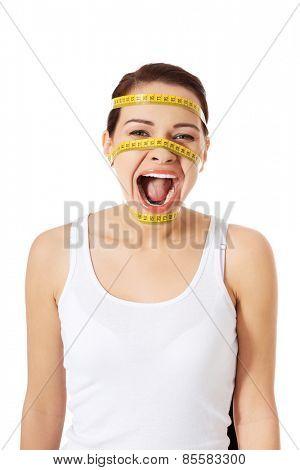 Caucasian woman with measuring tape around head.
