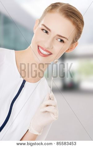 Young dentist with small mirror to checking up teeth