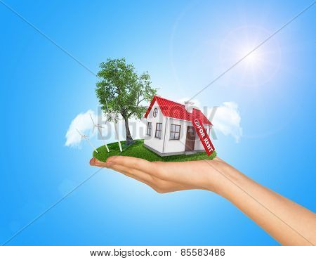 White house in hand for sale with red roof and chimney. Background sun shines brightly on right