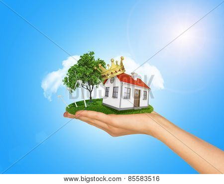 White house in hand for sale with red roof, crown, chimney. Background sun shines brightly on right