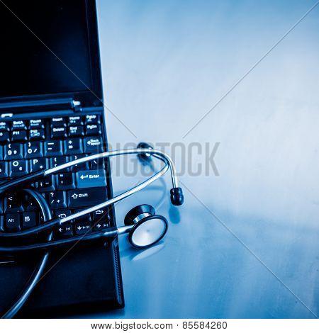 Electronic medical, stethoscope on PC/Laptop/Keyboard blue toned images.