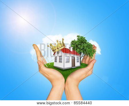 Hands holding house on green grass with crown, red roof, chimney, tree, wind turbine. Background clo