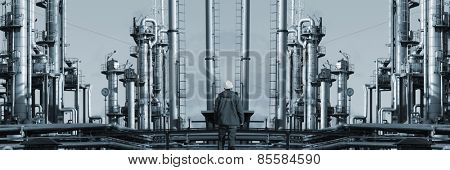 oil worker in front of giant refinery, mirror image concept