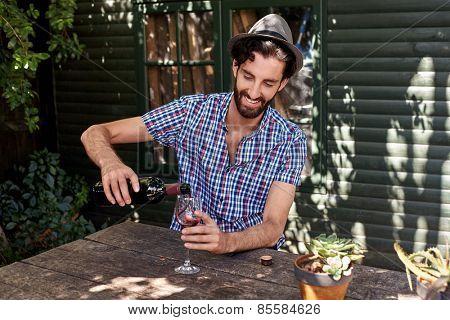 young man enjoying red wine outdoors in summer spring season backyard garden at home