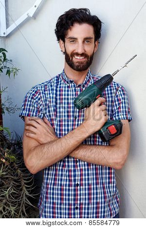 portrait of man using cordless battery drill for outdoor home improvements
