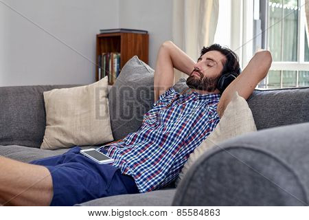 man listening to music relaxing on sofa couch in home living room
