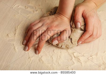 Making dough by female hands on wooden table background