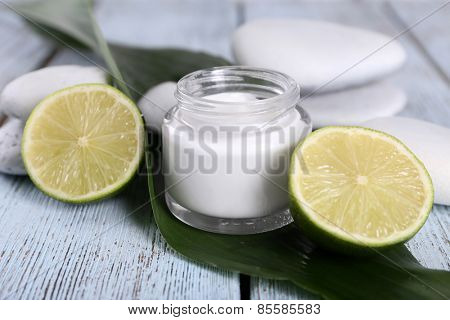 Cosmetic cream with half lime and spa stones on wooden background