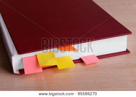 Book with bookmarks on wooden table