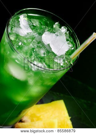 Green drink  with crushed ice on dark background. Top view. Glass tilted