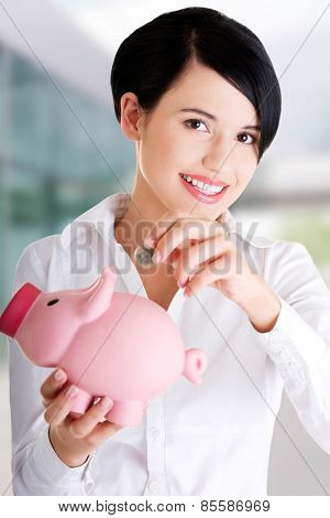 Happy businesswoman putting an euro coin into piggy bank