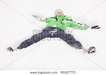 Young Boy Playing In Snow Lying On His Back
