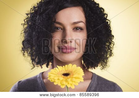 Close up of a joyful woman being happy and holding a flower in her hand, isolated on yellow background.