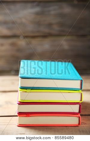 Colorful notebooks on old wooden table