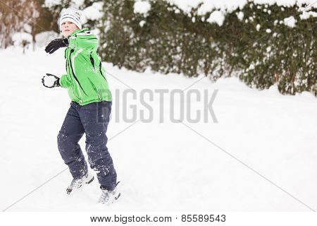 Young Boy Enjoying A Winter Snowball Fight