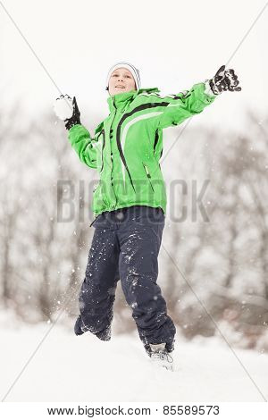Happy Young Boy Having A Snowball Fight