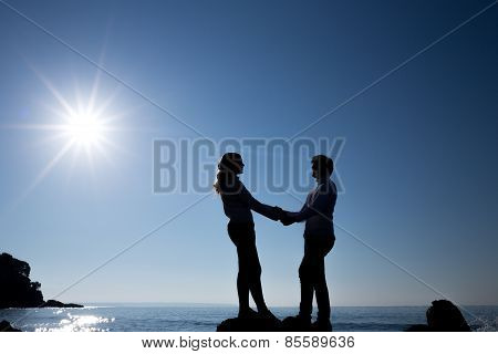 silhouette of teenager couple in front of a beautiful sky