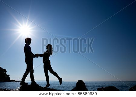 silhouette of happy teenager couple on the beach