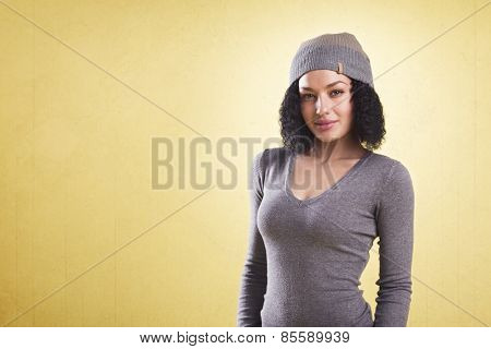 Smiling cool girl standing in front of yellow background representing young generation, with empty copy space.