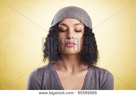 Cool woman looking down with woolen cap, representing young generation, isolated on yellow background.
