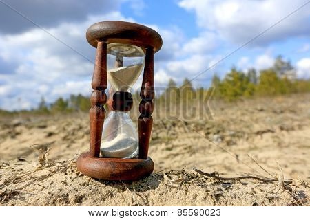Hourglass on sand in forest