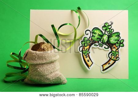 Greeting card for Saint Patrick's Day with horseshoe and bag of coins on green background
