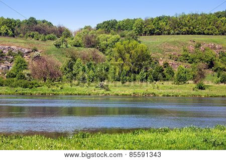Landscape Of A Green Grassy Hills, Trees, River And Sky