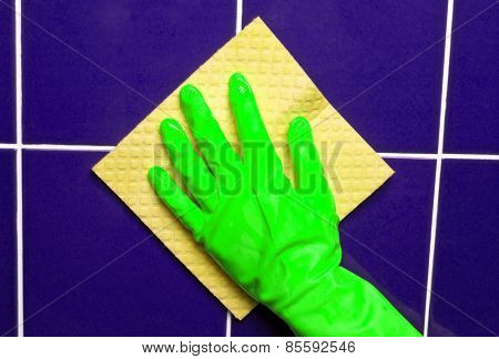 Hand with yellow sponge cleaning the bathroom tiles
