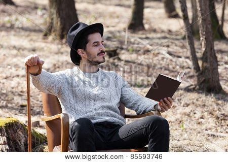 man reading a novel in the woods, portrait