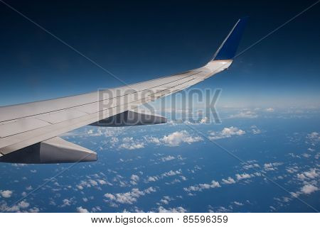 Airplane Wing Above The Ocean Blue