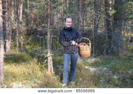 Young woman with a basket of cepes mushrooms in the forest