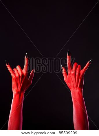 Red spooky hands showing heavy metal gesture, Halloween theme, copy-space for your text