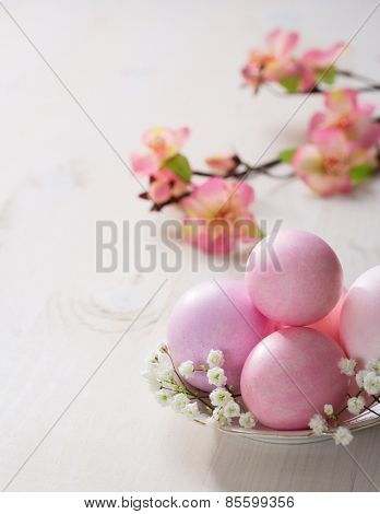 Plate  with pink   Easter eggs on wooden table. Focus on the  Easter eggs
